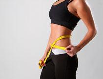 软尺放腰间的运动美女高清图片