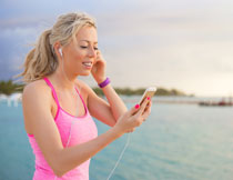 手拿着手机的跑步美女高清图片