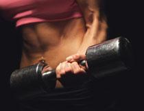 紧握着哑铃的肌肉人物特写图片