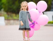 手里抓着很多气球的小女孩图片
