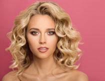 粉色背景前的金发美女高清图片
