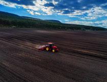 山坡农田上作业的农机高清图片