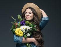 抱着花的惬意美女摄影高清图片
