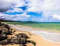 岩石与涌向海滩的潮水高清图片