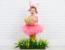 抱一篮子彩蛋的小女孩高清图片