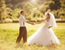 草丛中的新娘新郎人物摄影图片