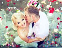 飘落花瓣下的新娘新郎高清图片