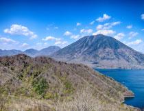 蓝天云朵与连绵的山丘高清图片