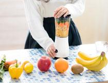 在榨蔬菜水果汁的美女高清图片