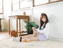 靠墙坐的看书女孩摄影高清图片
