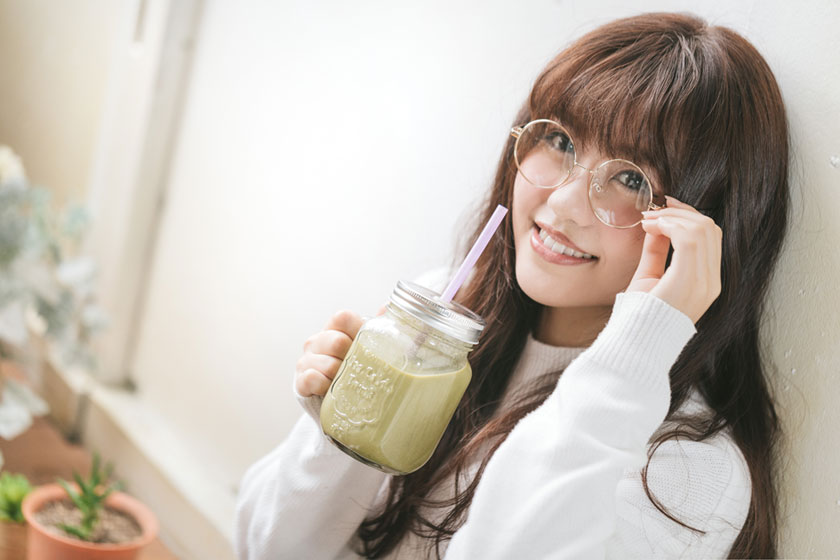 喝果汁的眼镜女孩摄影高清图片