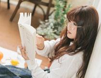 靠墙在看书的美女摄影高清图片