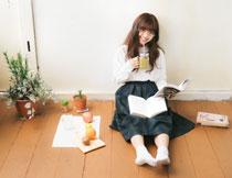 靠墙坐着看书的女孩摄影高清图片