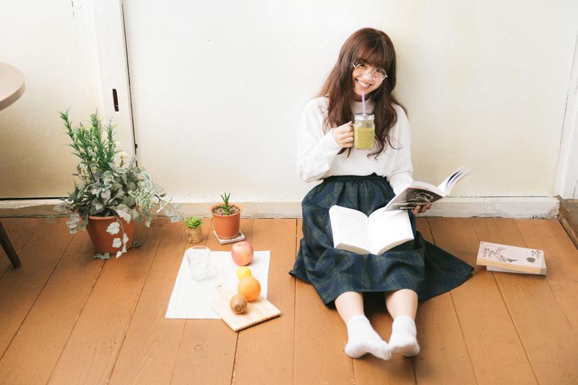 靠墙坐看书的女孩摄影高清图片