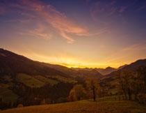夕阳霞光山间植被摄影高清图片
