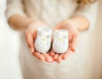 双手捧着小鞋子的孕妇高清图片