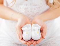 孕妇手中的小鞋子特写高清图片