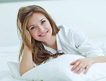 床上歪着头的美女摄影高清图片