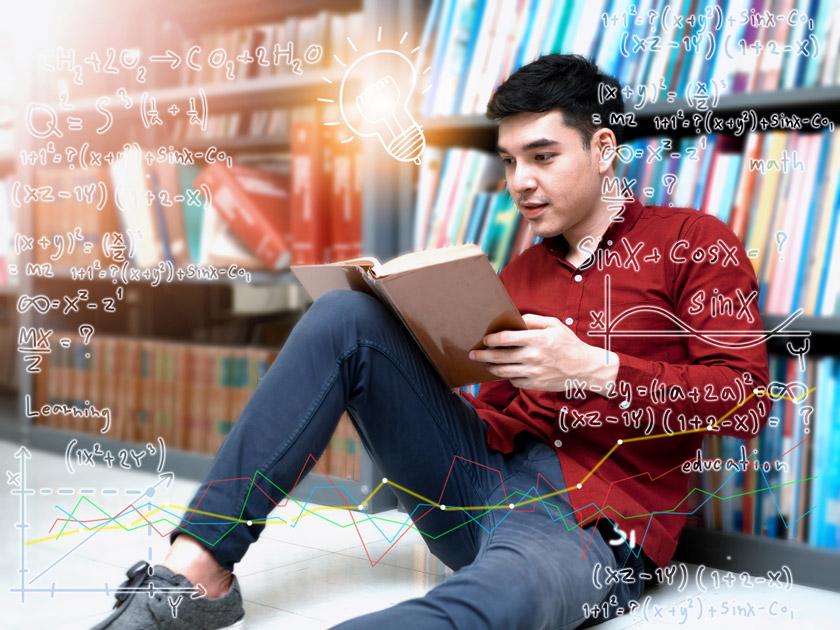 靠着书架看书的男学生高清图片