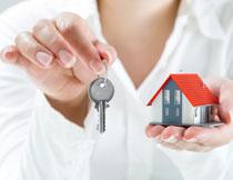 手中的钥匙与房子模型高清图片