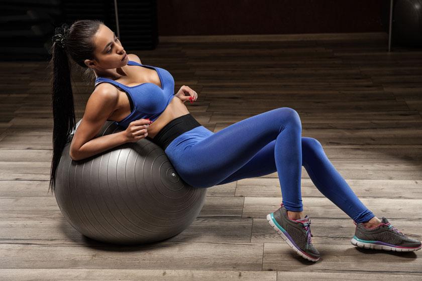 背靠健身球的美女摄影高清图片