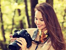 手拿相机的披肩发美女摄影图片